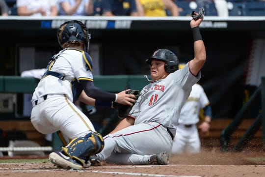 Jun 21, 2019; Omaha, NE, USA; Texas Tech Red Raiders infielder Cameron Warren (11) slides home ahead of the tag from Michigan Wolverines catcher Joe Donovan (0) in the second inning against in the 2019 College World Series at TD Ameritrade Park. Mandatory Credit: Steven Branscombe-USA TODAY Sports