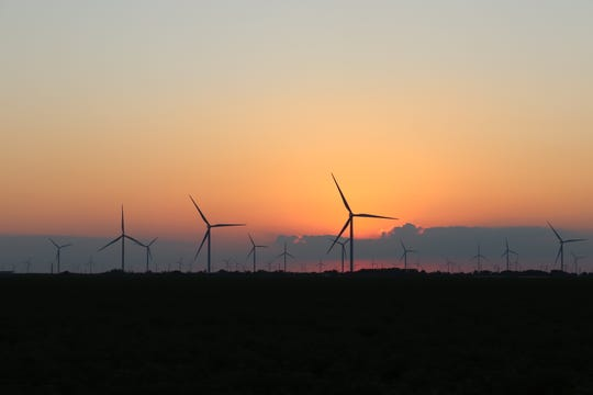 Wind turbines spin at sunset in South Texas.