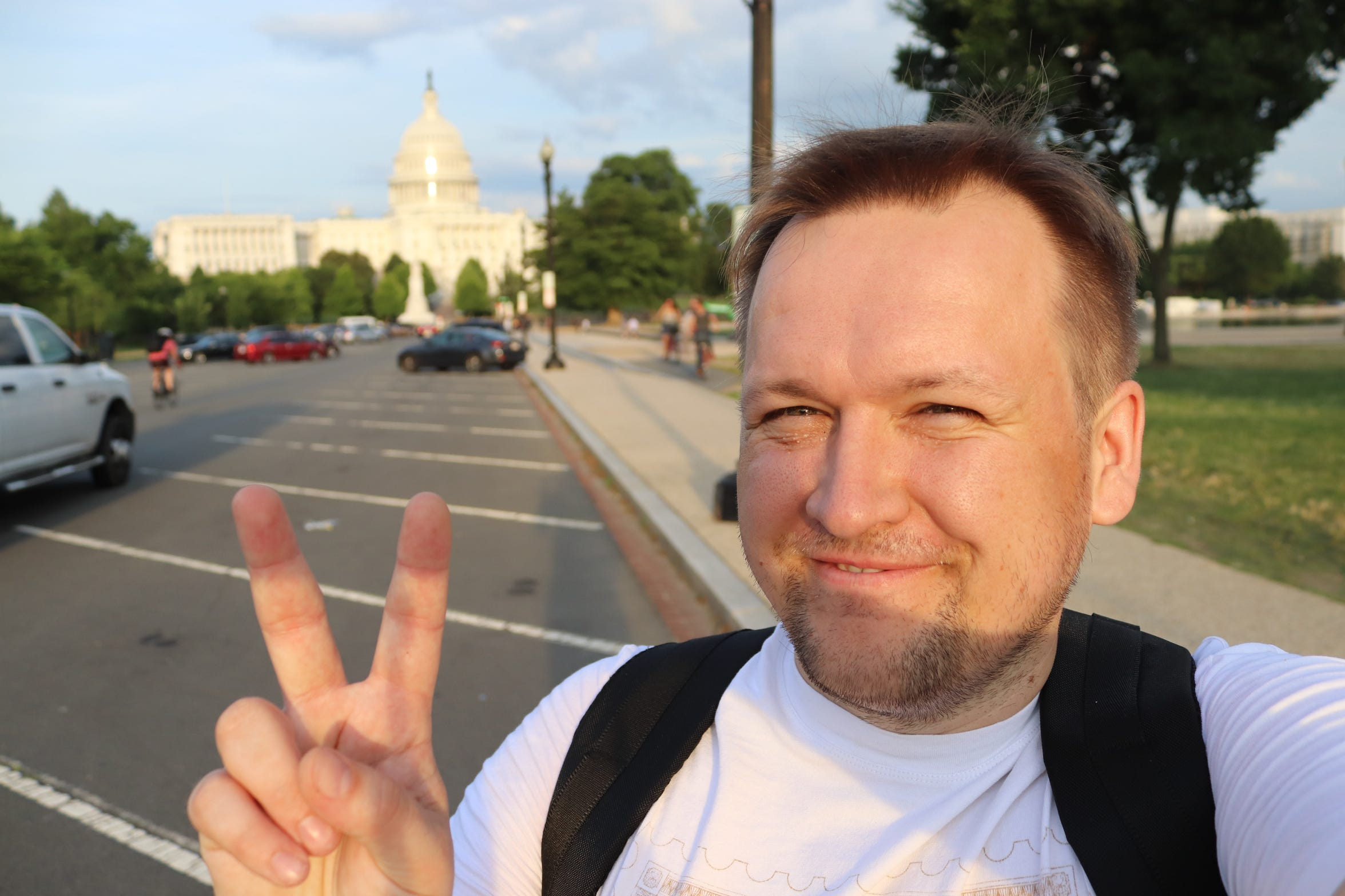 Pavel Alekseev flashes the peace sign near the White House.