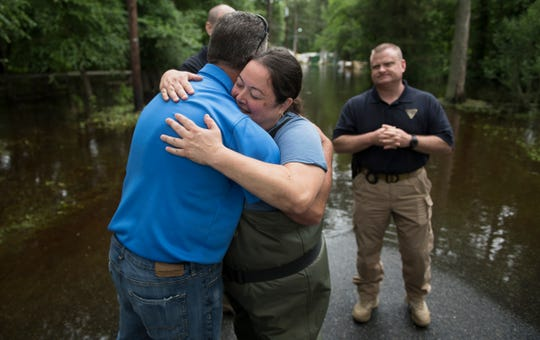 Southampton Township flood victim Orly Buday, center, hugs Burlington County Freeholder Latham Tiver, left, after Tiver and New Jersey State Police Lt. William Craney, right, visited Southampton Township with other officials on Friday, June 21, 2019 to offer support to flood victims.