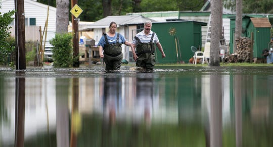 Southampton Township Mayor Jim Young and Southampton Township flood victim Orly Buday walk through a flooded portion of Crystal Road in Southampton Township after Young visited Buday's flooded Southampton Township home on Friday, June 21, 2019.