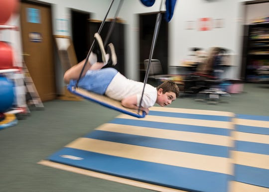 Cole Wright, 12, enjoys flying through the air during a therapy session with Maria Dudzinski Thursday morning during the Pioneer Summer Therapy Program.