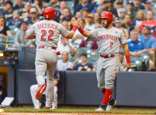 Cincinnati Reds second baseman Derek Dietrich (22) high fives third baseman Eugenio Suarez (7) after scoring a run during the first inning against the Milwaukee Brewers at Miller Park.