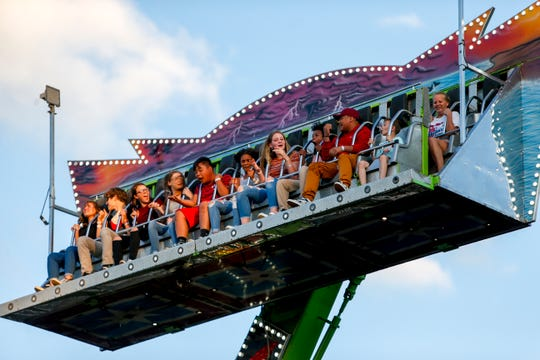 Fairgoers are taken on a spin up and down on a ride at the Montgomery County Fair at Clarksville Speedway & Fairgrounds on June 20, 2019.