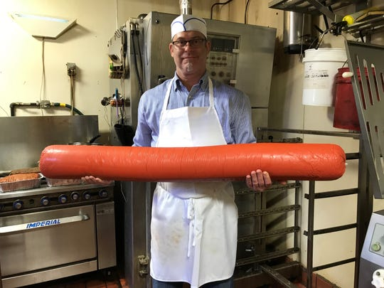 Leszek 'Jabi' Jablonski holding the contender for the world's largest hot dog.
