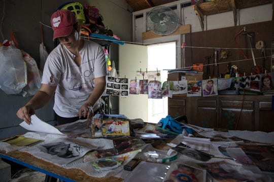 Kayci Dickerson holds back tears as she goes through the tedious process of sorting her photos and hanging them to dry. Kayci, who lives with her husband Vic Jr. and their three kids had to flee their home as flood waters broke down the wall to their basement.