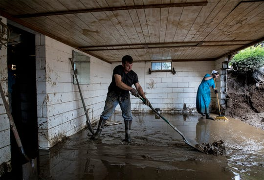 Matt Hershberger and Violet Miller, both from Bakersville, help clean up the house of Wilson McCoy in West Lafayette after the basement wall gave way during heavy rains.