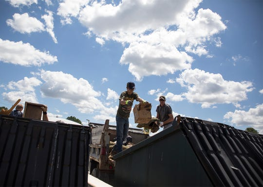 James Ornand (left) and Chad Wilson both volunteered their Friday helping haul and unload trucks and trailers filled with garbage from the floods in West Lafayette.