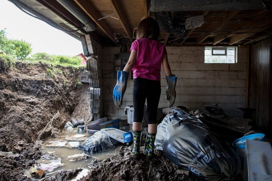 Vayda Dickerson, 6, surveys the damage done in her basement after heavy rains caused the basement wall to collapse.