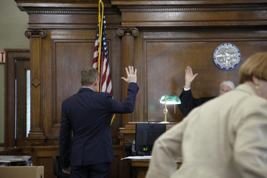 Chris Godfrey, a former Iowa Workers' Compensation Commissioner who is suing former Gov. Terry Branstad for discrimination, is sworn in as a witness at the Jasper County Courthouse on Friday, June 21, 2019.