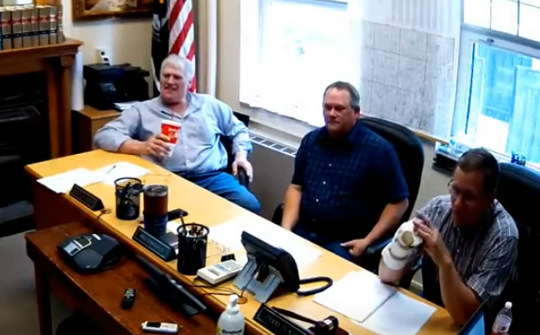 Police say Winnebago County Supervisor Mike Stensrud, left, seen in a image from video, drank alcohol from a cup during a May 21 supervisor meeting.
