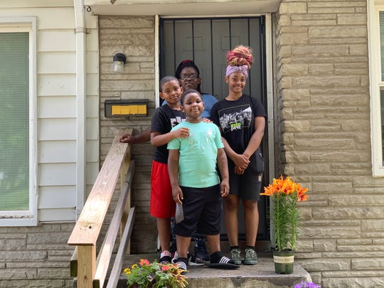 Detroiter Sabrina Beal with children Ajanae Beal, 16, Armanii Beal, 9, and Emanuel Wilson, 6, in front of their new home on Detroit's west side on June 19.