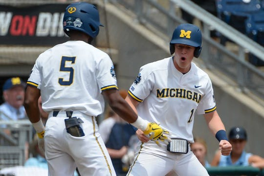 Michigan first baseman Jimmy Kerr (15) celebrates scoring in the first inning with Wolverines outfielder Christan Bullock (5) against Texas Tech in the 2019 College World Series at TD Ameritrade Park.
