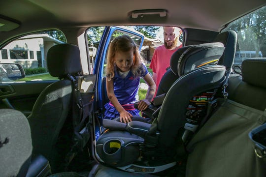 Daniel Long, 38, helps his daughter Alice Long, 5, into her car seat in their 2019 Ford Ranger Supercrew cab at their home in Southfield, Mich. on Friday, June 21, 2019.