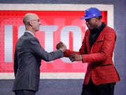 NBA Commissioner Adam Silver, left, greets Sekou Doumbouya, of France, after the Detroit Pistons selected him as the 15th pick overall in the NBA basketball draft Thursday.