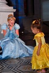 Costumed Cinderella greets a young guest.