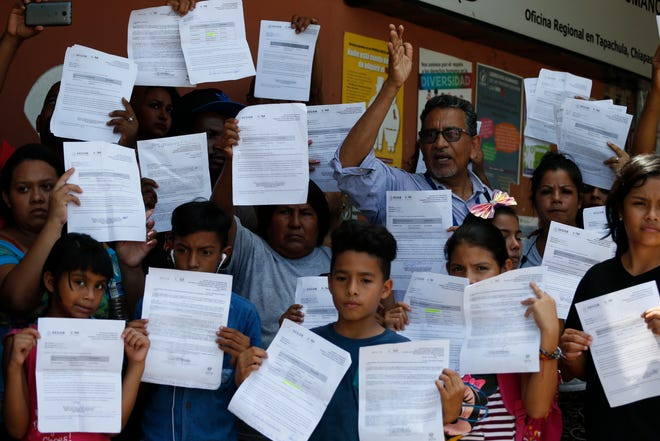 Human rights activist Luis Villagran speaks as migrants hold up their Mexican migration paperwork during a small protest against long wait times for receiving documents to legally stay in Mexico, outside the office of the national Human Rights Commission in Tapachula, Mexico, Wednesday, June 19, 2019.