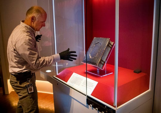 Mike Casey, Exhibits Project Manager at the Abraham Lincoln Presidential Museum, moves the newly acquired Bible, into an exhibit at the museum. (Ted Schurter/via AP)