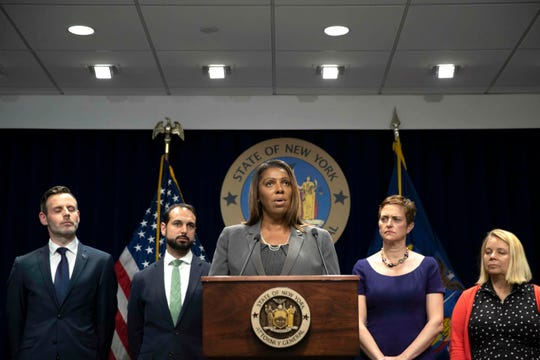 A group of state attorneys general, including New York's Letitia James, center, filed a lawsuit Tuesday to block T-Mobile's $26.5 billion bid for Sprint, citing consumer harm.