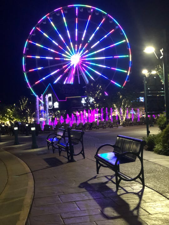 The Pigeon Forge Smoky Mountain Wheel lights up The Island entertainment area at night.