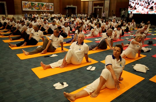 Diplomats of various countries perform yoga to mark International Yoga Day in New Delhi.