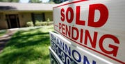 "A house with a ""sold pending"" sign fixed on the realtor's sign."