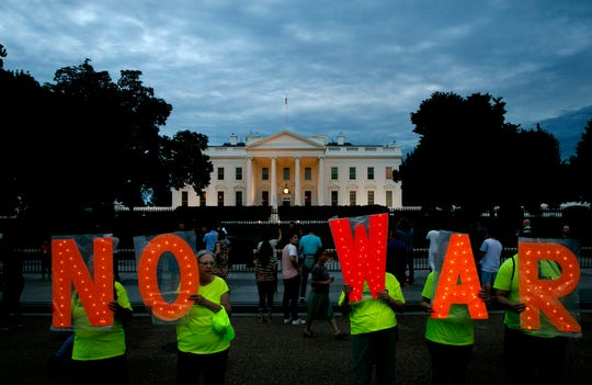 """Protesters outside the White House, Thursday June 20, 2019, in Washington, after President Donald Trump tweeted that """"Iran made a very big mistake"""" by shooting down a U.S. surveillance drone over the Strait of Hormuz in Iran."""