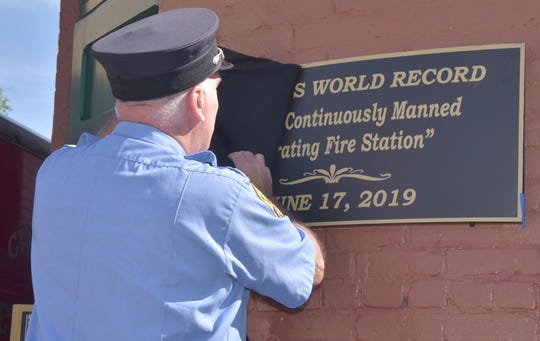 """Firefighter Fred LaPoint unveils a plaque recognizing the Guinness World Record's designation of the Manistee Fire Department as the """"Oldest Continuously Manned Operating Fire Station"""" on its 130th birthday on Friday. He worked two years to create and win the world record designation."""