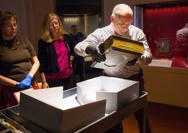 Mike Casey, Exhibits Project Manager at the Abraham Lincoln Presidential Museum, moves the newly acquired Bible into an exhibit at the museum. Abraham Lincoln Presidential Library and Museum Conservator Bonnie Parr and Carla Smith, registrar for the Abraham Lincoln Presidential Library and Museum, are at left.