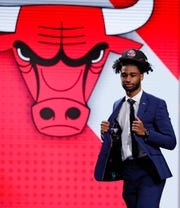 North Carolina's Coby White walks onstage after the Chicago Bulls selected him as the seventh overall pick.