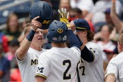 Michigan's Jimmy Kerr, left, is greeted by Jack Blomgren (2) and Jesse Franklin (7) at the dugout after scoring against Texas Tech on Friday.