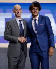 NBA Commissioner Adam Silver, left, poses for photographs with Michigan's Jordan Poole after the Golden State Warriors selected him as the 28th pick.