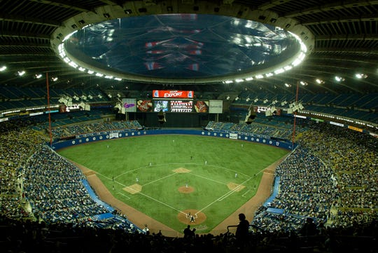 FILE - In this Sept. 29, 2004, file photo, fans watch a baseball game between the Montreal Expos and Florida Marlins at Olympic Stadium in Montreal. The Tampa Bay Rays have received permission from Major League Baseball's executive council to explore a plan that could see the team split its home games between the Tampa Bay area and Montreal, reports said.