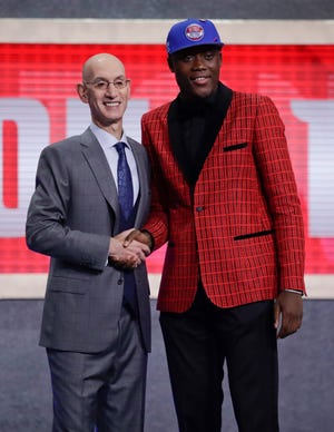NBA Commissioner Adam Silver, left, poses for photographs with Sekou Doumbouya, of France, after the Detroit Pistons selected him as the 15th pick overall.