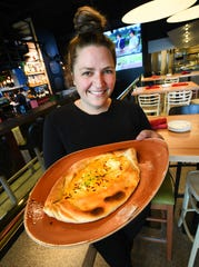 Chef and owner Emmele Herrold holding a hot plate of Georgian Cheese Bread with egg, chive and red pepper flakes.