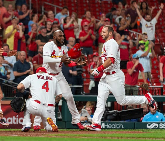 St. Louis Cardinals' Paul Goldschmidt, right, is greeted by teammates Yadier Molina, left, and Marcell Ozuna after he hit the game winning home run in a baseball game against the Miami Marlins, Wednesday, June 19, 2019, in St. Louis. Cardinals won 2-1. (AP Photo/L.G. Patterson)