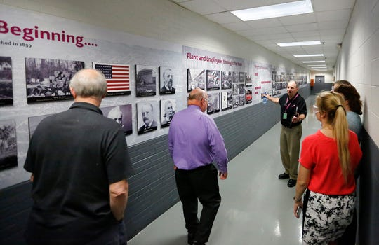 Peter Beyer of Fives Giddings & Lewis explains a wall showing the history of the company June 20, 2019 at an open house in Fond du Lac, Wis.