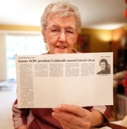 Judy Goldsmith holds up a Fond du Lac newspaper clipping from when she was named interim dean at University of Wisconsin-Fond du Lac in 1993. Photo was taken June 21, 2019.