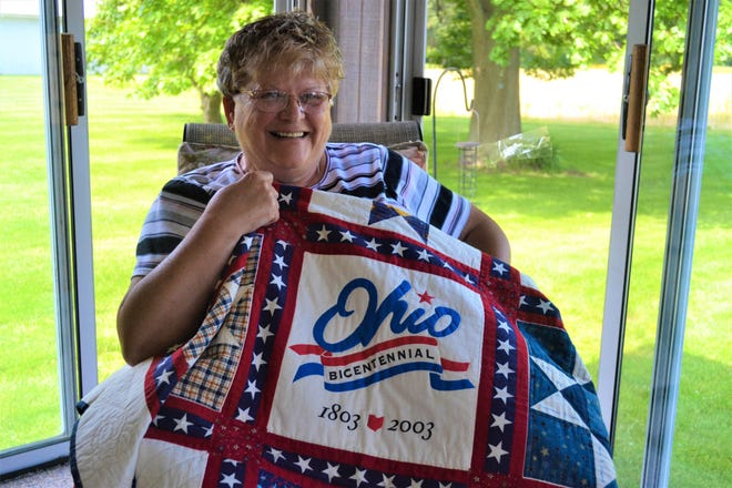 Krista Michaels with one of the thousands of quilts she has made. This one features one of her favorite themes: red, white, and blue historic stars.