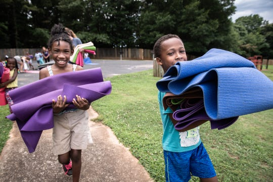 Aliyah McIntyre, 7, and Mijiyuan Fairfax, 7, help carry yoga mats to the car of Amy Starkey, owner of Yoga-2-Go after she finished leading a yoga class at Shemwood Crossing apartments as part of a Greenville County Schools summer program Thursday, June 20, 2019.