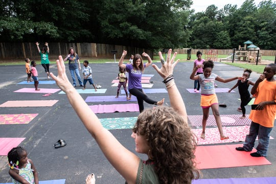 Amy Starkey, owner of Yoga-2-Go, leads a yoga class at Shemwood Crossing apartments with children who reside there as part of a summer program run by Greenville County Schools Thursday, June 20, 2019.