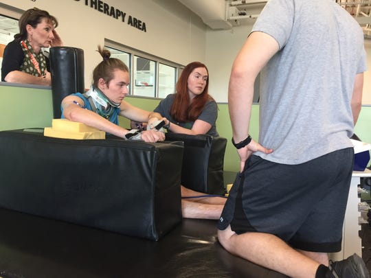 From left, Jaelene Johnson watches son Jack Racicot in physical therapy as he is being helped by Alex Muscarello and Lane Baker.