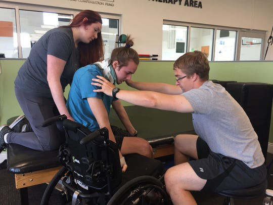 Jack Racicot is helped out of his wheelchair for physical therapy by occupational therapist Alex Muscarello, left, and intern Lane Baker.