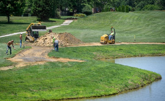 Workers with Bennett & Sons Paving prepare the cart paths for resurfacing around holes 15 and 16 at the city-owned Bridges Golf Course of Henderson, formerly the Players Club of Henderson on Wednesday, July 12, 2019.