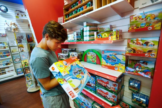 Max Lauer looks at some of the Hape products for sale at Kits & Kaboodle in Carmel, Friday, June 21, 2019.  Lauer works at the store.  The company that sells Hape is German.  President Donald Trump's latest proposed tariffs on Chinese goods includes toys.  China makes 80% of toys sold in the U.S., according to the U.S. Department of Commerce.  Kits & Kaboodle sells many European-designed products from European companies, but many are made in China.  So the tariffs have this store doing early inventory and preparation for this year's holiday rush.