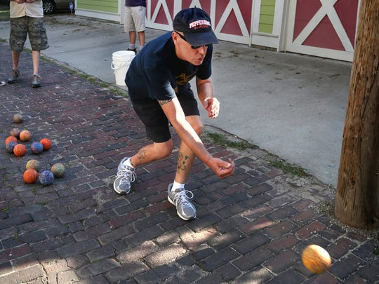 Jeff Ayers tosses his bocce ball down a brick-lined alley between Broadway Street and Park Avenue in 2014.