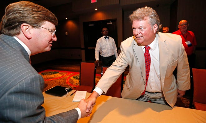 Gubernatorial candidates Attorney General Jim Hood, a Democrat, right, and Republican Lt. Gov. Tate Reeves shake hands during a Mississippi Press Association event last month in Biloxi. Reeves continues to raise more campaign money than his rivals, including Hood.