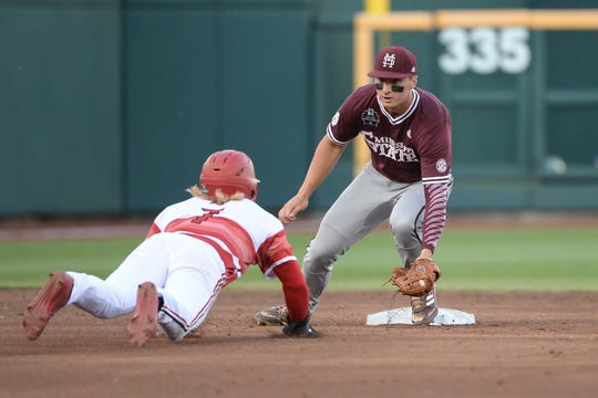 Mississippi State Bulldogs second baseman Justin Foscue (17) applies the tag on Louisville Cardinals infielder Lucas Dunn (7) in the third inning in the 2019 College World Series at TD Ameritrade Park.