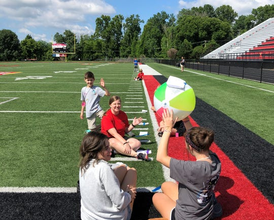 On the final day of STEAM camp, students tried to replicate on the Central High School football field the distances between planets in the solar system. The beach ball represented the sun and the campers tried to estimate how many steps between each planet. Pictured June 21, in foreground, Jake Iovine, with math teacher Cindy Blanchard and volunteers Lauren Turrentine and Emily Leach.
