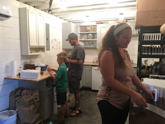 Honey Dew Naturals is very much a family affair. Nine-year-old Caleb Huff helps his parents, Nate and Alli, with labeling.